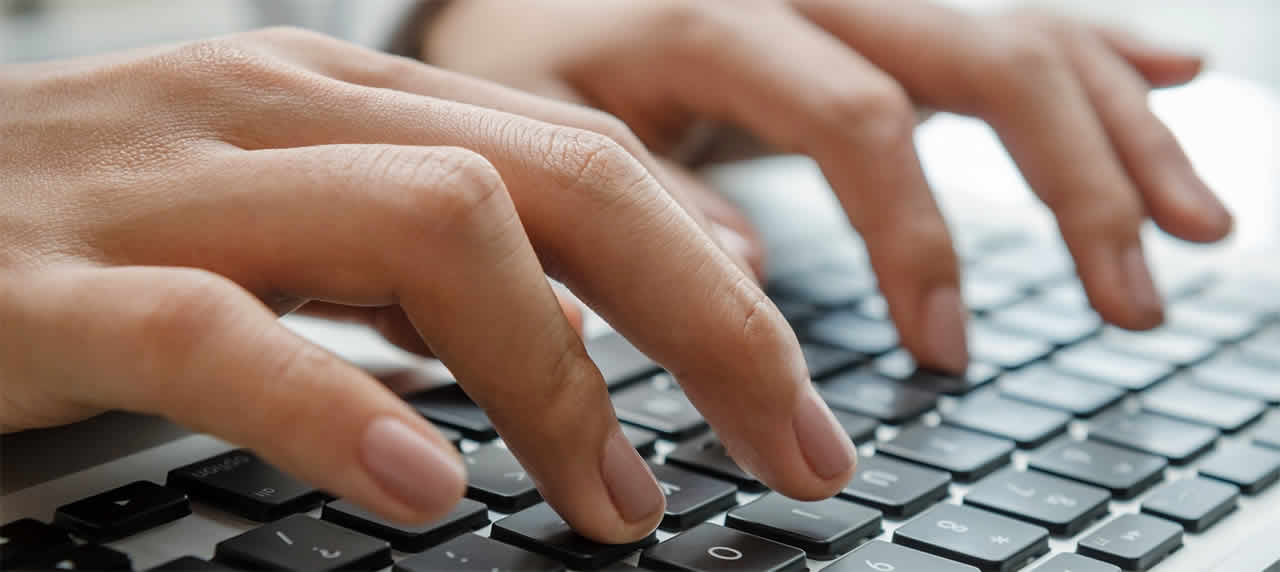 Photograph of hands typing on a keyboard