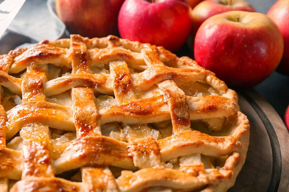 Cooked Apple Pie on a table with whole Apples